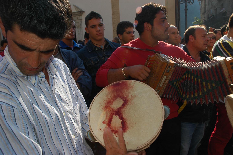 """Preso dal suono, quasi come in trans non si accorge della ferita e continua a suonare """"u tambureddru"""" fuori dal santuario di Polsi, Calabria"""
